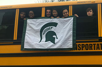 Group of alumni hanging a Spartan flag out a bus window
