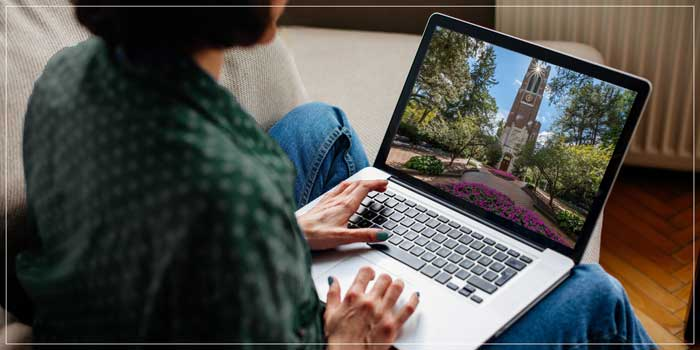 Woman on a laptop with a photo of Beaumont Tower